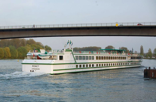 european river cruise ship under bridge